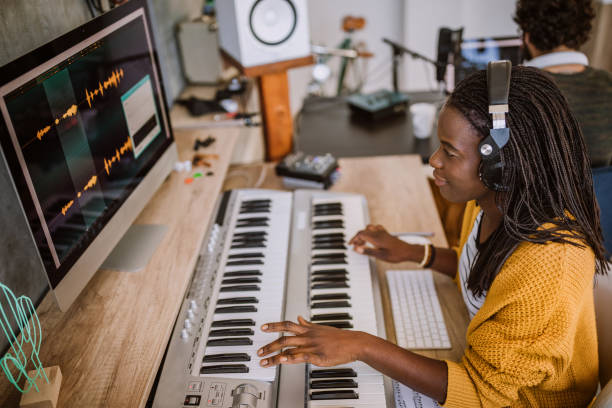 Couple making music in studio Young, multi-ethnic couple  making music in  studio, using modern technology electronic music stock pictures, royalty-free photos & images