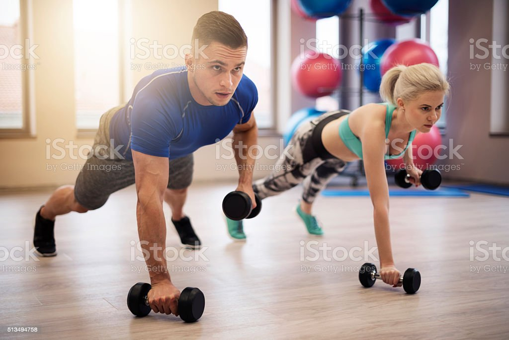 Couple making push ups with weights stock photo