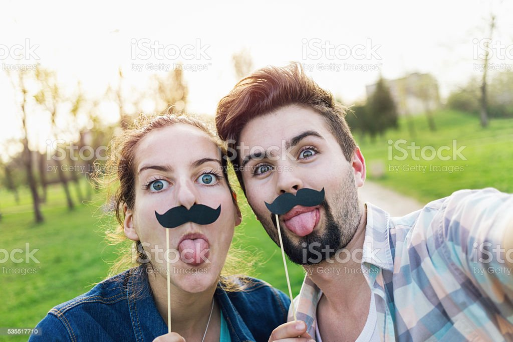 Couple making selfie with mustaches stock photo