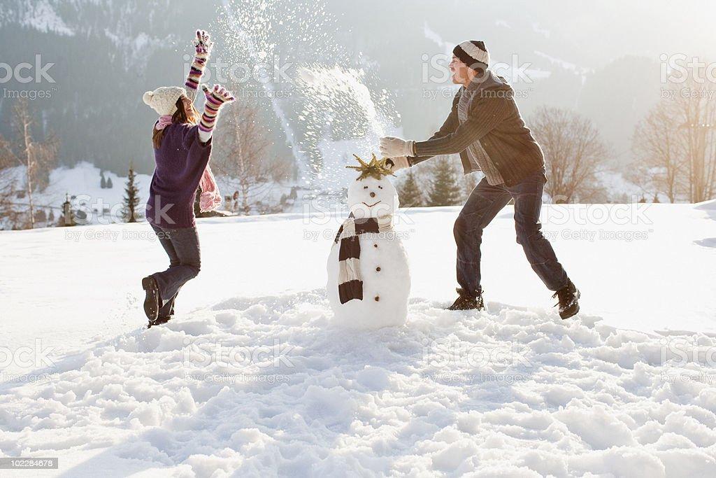 Casal fazendo um boneco de neve - foto de acervo