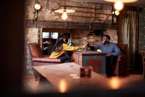 paar machen toast, wie sie sich für mittagsgetränke in traditionellen englischen pub - liebeskummer englisch stock-fotos und bilder