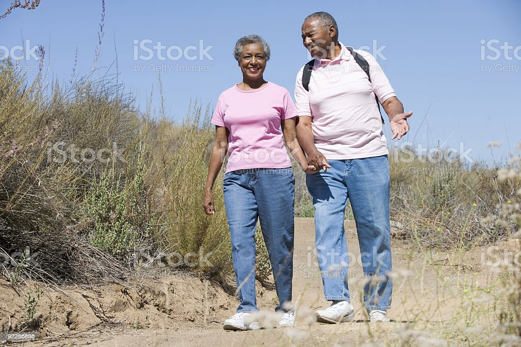 Couple male and female walk along sandy path stock photo