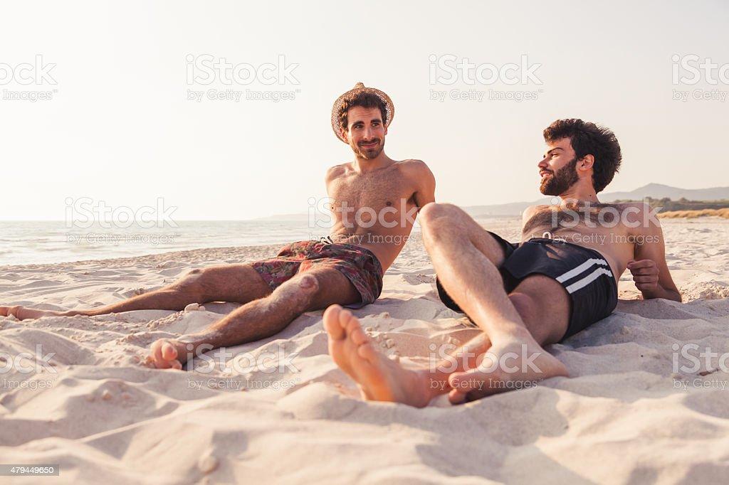 Paar männliche Freunde am Strand bei Sonnenuntergang – Foto