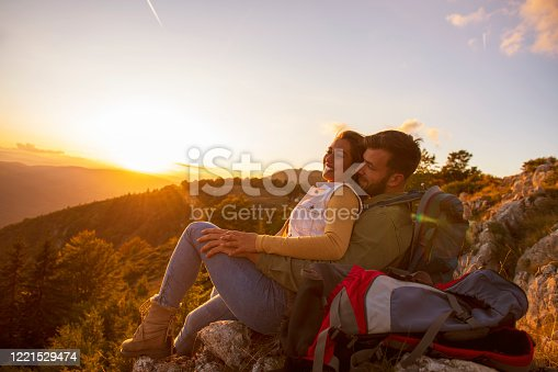 Couple Man and Woman sitting on cliff enjoying mountains and clouds landscape Love and Travel happy emotions Lifestyle concept. Young family traveling active adventure vacations.