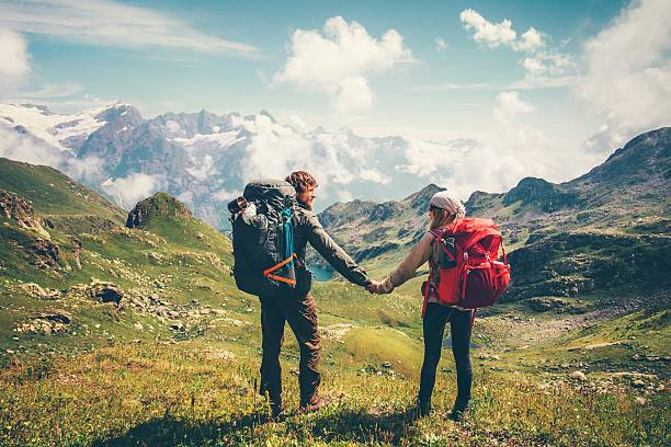 Couple Man and Woman Travelers with backpack holding hands hiking – Foto
