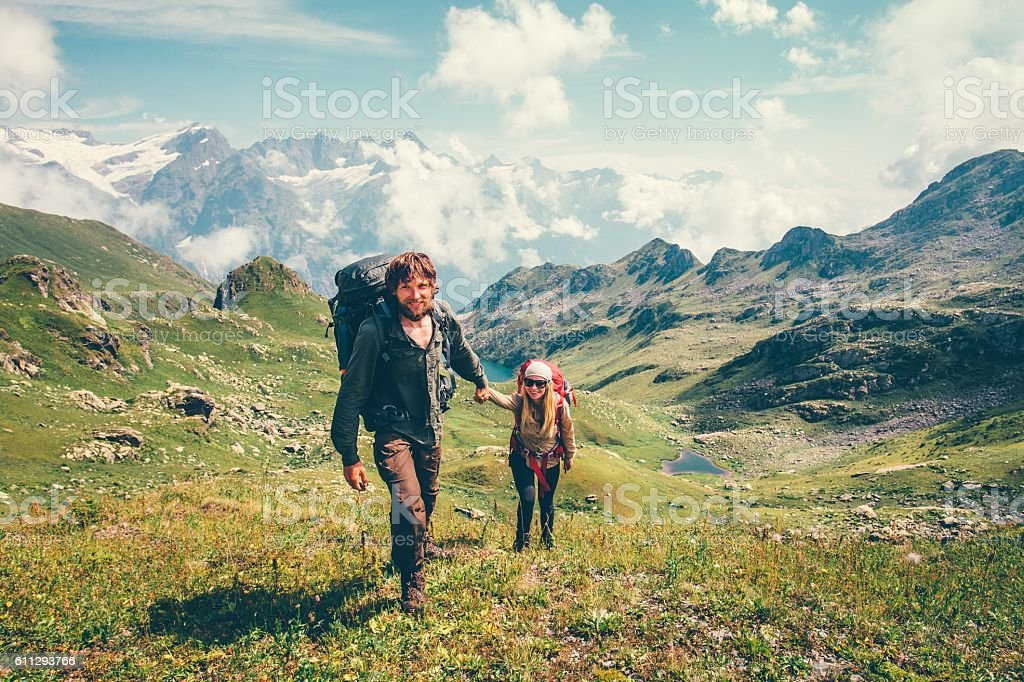 Couple Man and Woman Travelers with backpack holding hands mountaineering – Foto