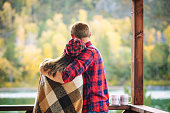 Couple man and woman young beautiful happy on the porch of a wooden house in nature with mugs of hot drinks