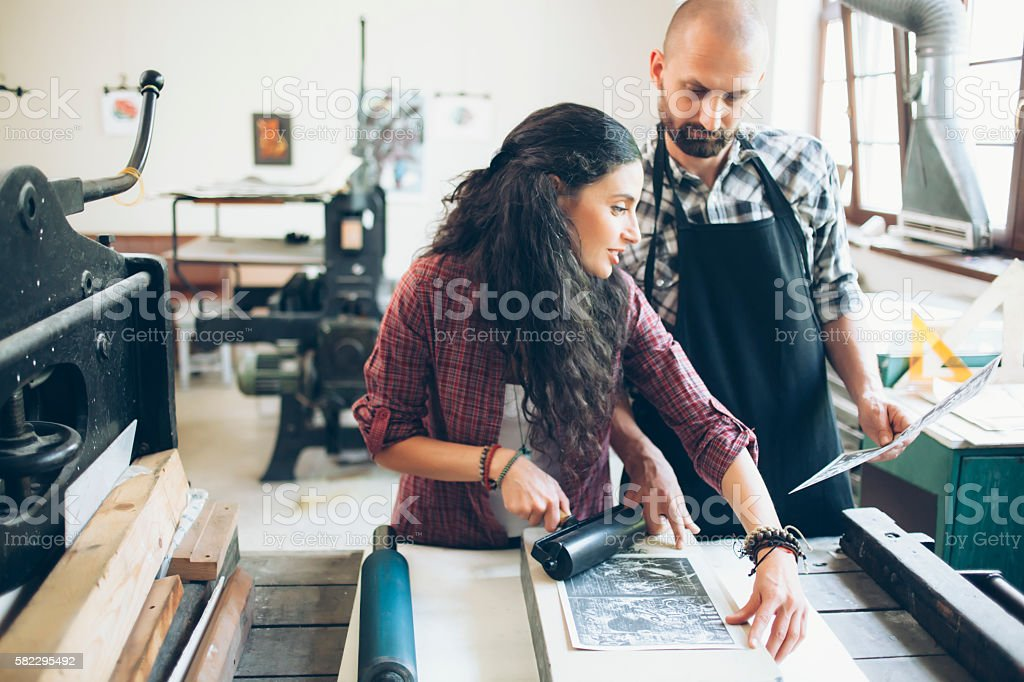 Couple manual workers at printing house stock photo