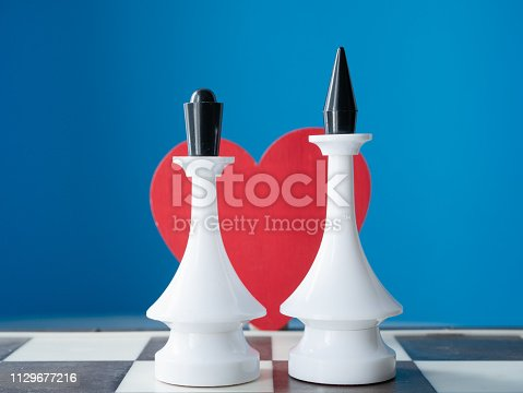 istock couple marriage wedding invitation idea. two chessman king and queen with red heart behind with blue background 1129677216