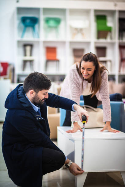 couple measuring  in furniture shop - furniture shopping stock photos and pictures