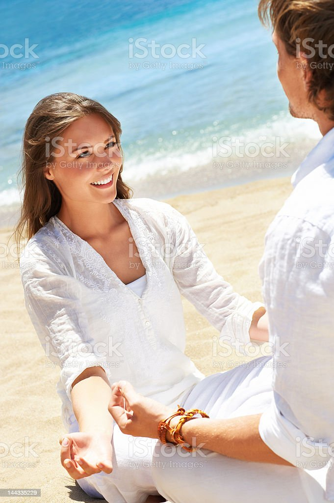 Couple meditating on the beach royalty-free stock photo