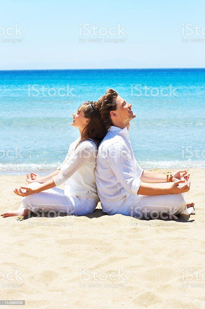 Couple meditating on the beach royalty-free stock photo