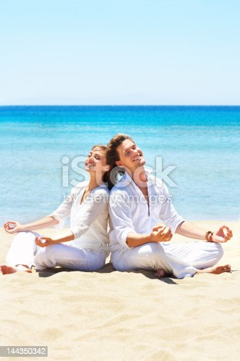 istock Couple meditating on the beach 144350342