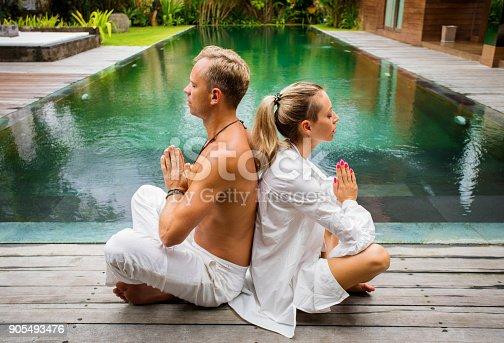 916126642istockphoto Couple meditating together and sitting in lotus pose 905493476