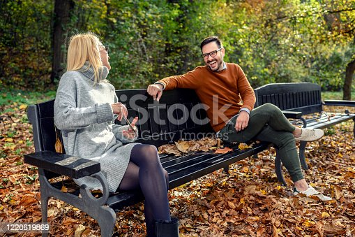 Woman and man in social distancing flirting sitting on a park bench