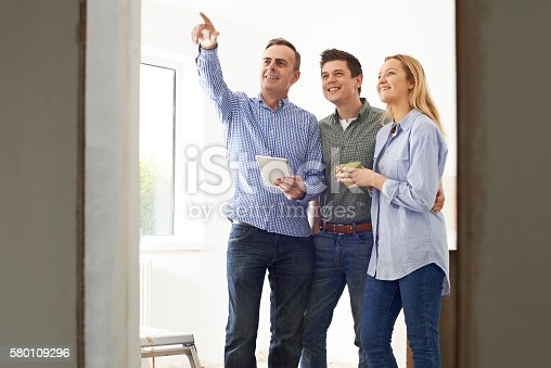 Couple Meeting With Architect Or Builder In Rennovated Property