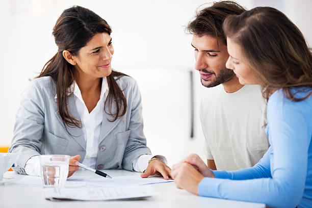 couple meeting with financial advisor - stock broker stock photos and pictures