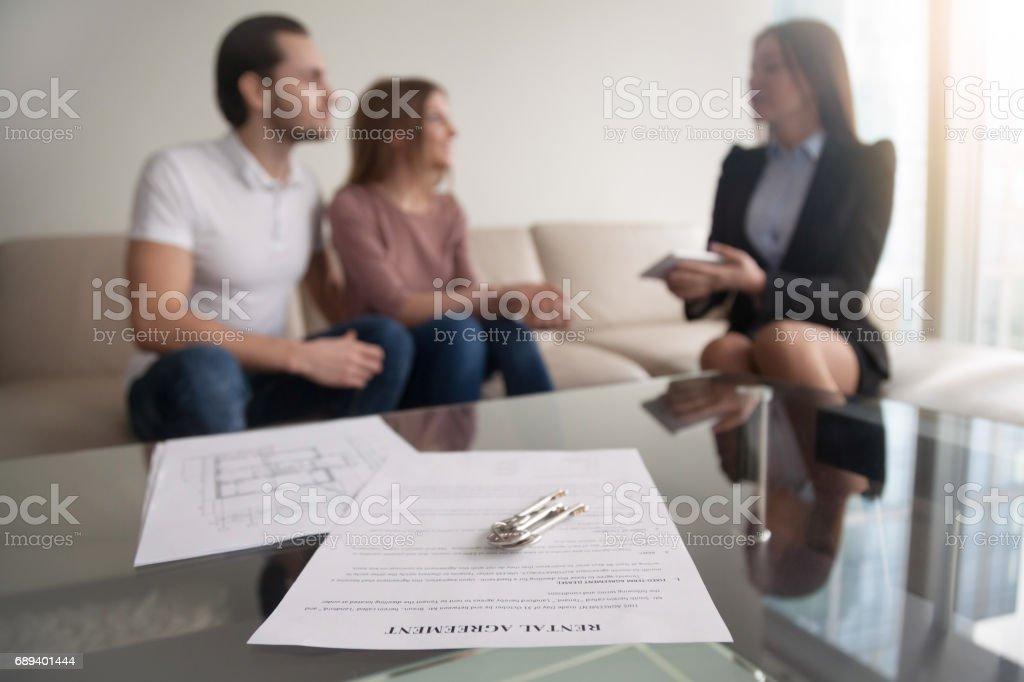 Paar ontmoeting met makelaar, focus op huurovereenkomst en sleutels foto
