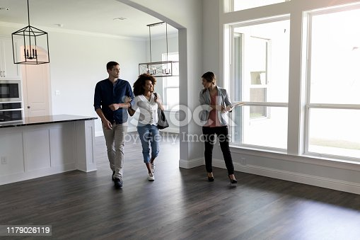 Realtor shows a couple a home. The realtor shows them the home's  large living and kitchen area. The couple is expecting their first child.