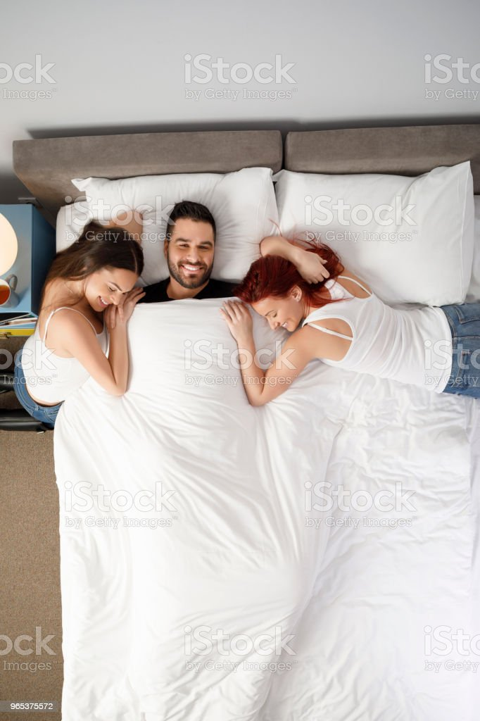 Couple men and two woman, best friends.  Weekend Activities,  In Bed,  Retro style hotel bedroom. Directly Above. royalty-free stock photo