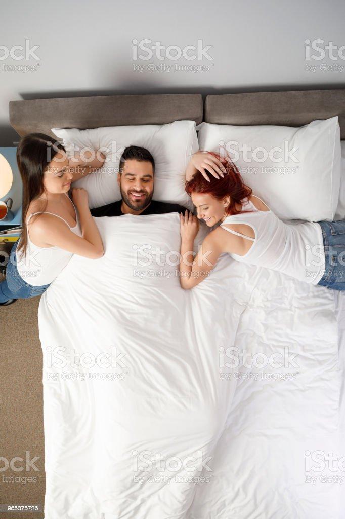 Couple hommes et deux femmes, meilleures amies.  Chambre d'hôtel week-end activités, dans le lit, style rétro. Directement au-dessus. - Photo de Activités de week-end libre de droits