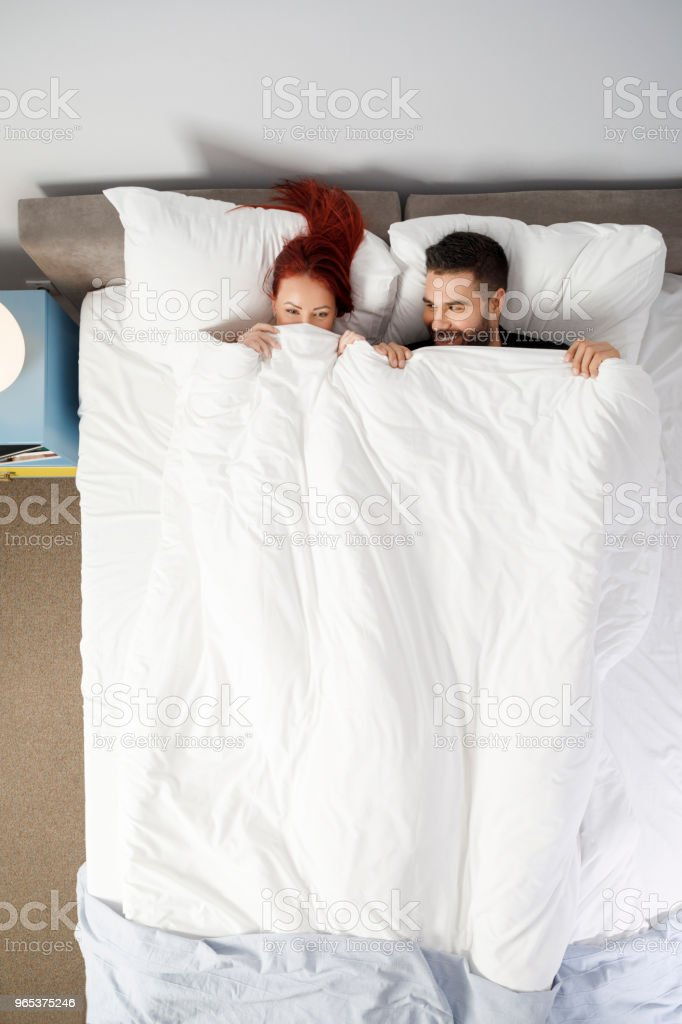 Couple men and woman, best friends.  Weekend Activities,  In Bed,  Retro style hotel bedroom. Directly Above. zbiór zdjęć royalty-free