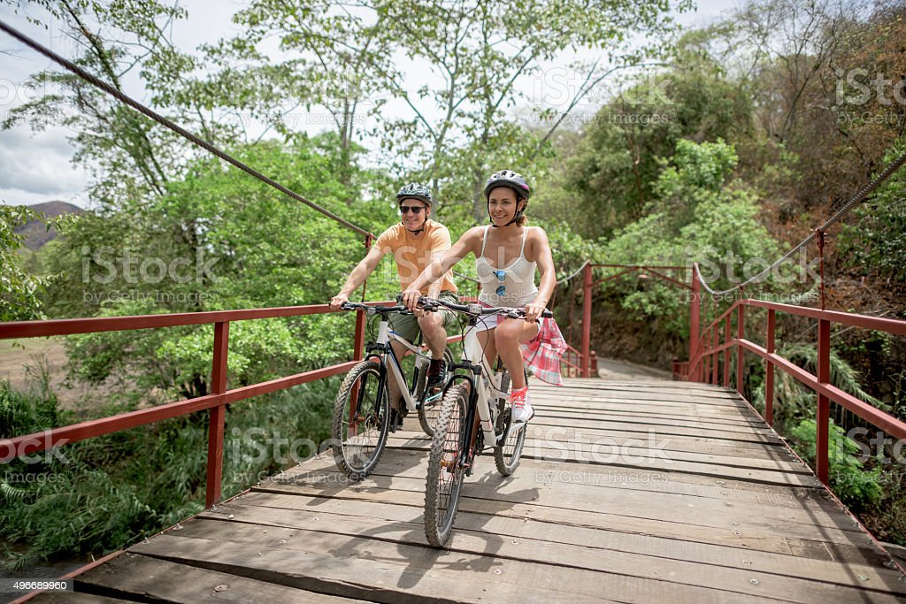 Couple mountain biking crossing a bridge royalty-free stock photo