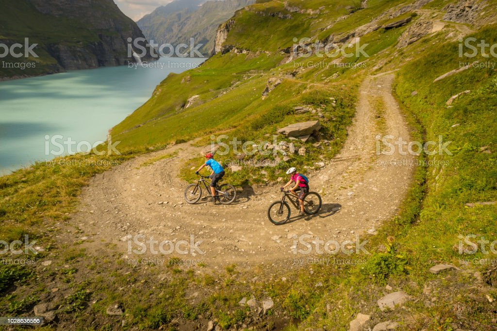 Couple Mountain Biking In Alpine Scenery Switzerland Stock