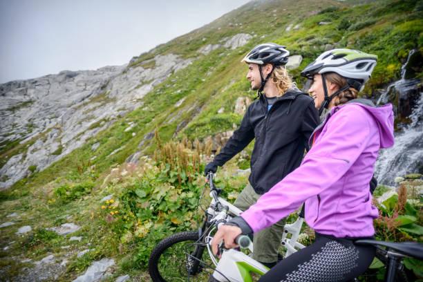 Couple Mountain Biking in Mountains stock photo