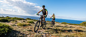 Young couple mountain biking on landscape, sea in background.