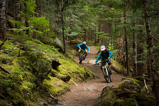 Couple mountain biking through a forest Couple mountain biking through a forest mountain biking stock pictures, royalty-free photos & images