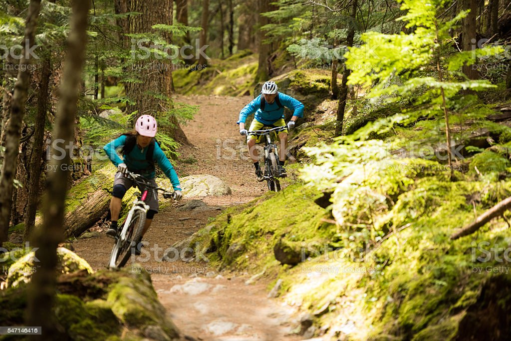 Couple mountain biking through a forest stock photo