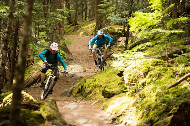 couple mountain biking through a forest - mountain biking stock photos and pictures