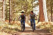 Couple mountain biking through forest, California