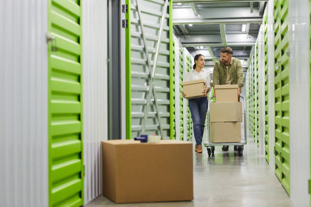Couple Moving Boxes in Storage Unit stock photo