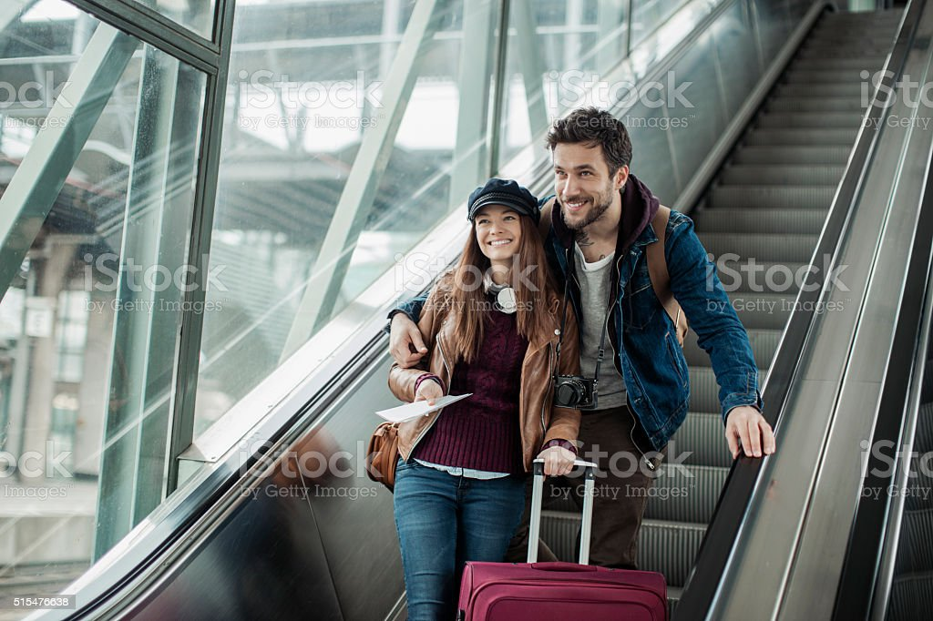 Couple moving down escalator stock photo