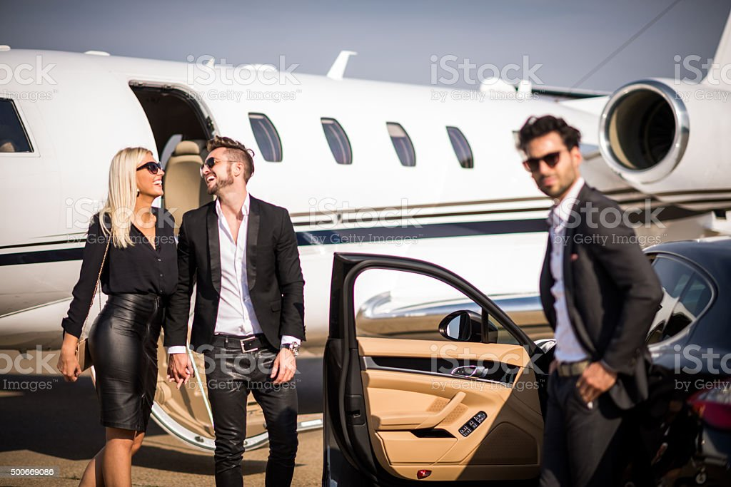 Couple moving from airplane to black car stock photo