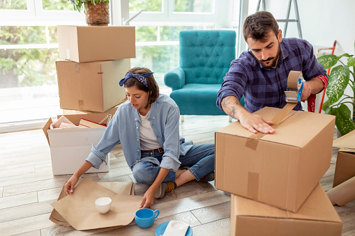 Couple in love packing things into cardboard boxes, getting ready for relocation - man taping boxes using packing machine while woman is wrapping fragile things into paper