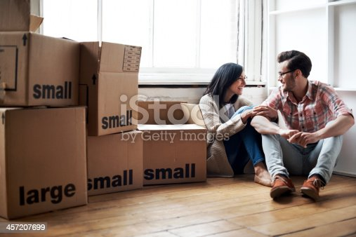 Couple relaxing after moving into new cozy loft apartment