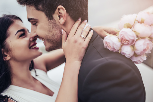 Just married! Portrait of beautiful young romantic couple is hugging and enjoying being together. Attractive woman in wedding dress with bridal bouquet in hands and handsome man in suit are celebrating wedding day. Ready for Honeymoon.