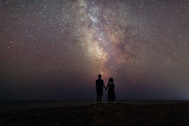 couple near the sea under the starry sky - gute nacht liebe stock-fotos und bilder