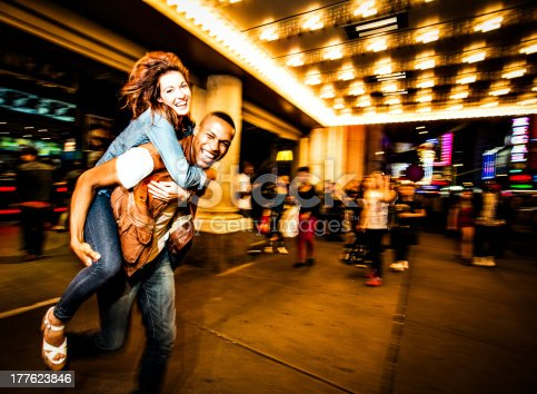 Couple having fun at night on Broadway, New York City.