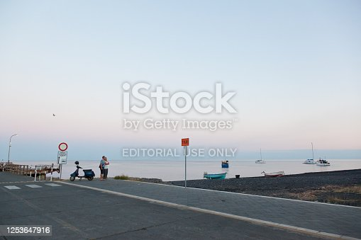 It's relaxing to look at the sea from the main pier in Stromboli. Many come heir for a scroll around sunset or at dusk. A couple is standing embraced next to an empty taxi stand in peace.