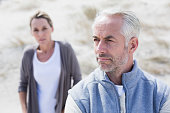 Couple not talking after argument on the beach on a bright but cool day