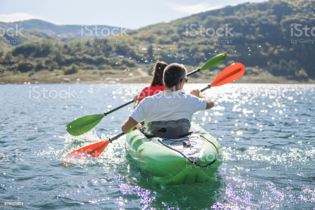 Couple oaring in the kayak stock photo