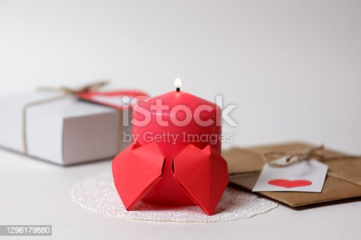 Couple of 3D red paper hearts, burning pink candle on white openwork paper napkin, gifts with labels, hearts closeup view selective focus. Love, Valentine's, women's day, relations, romantic concept
