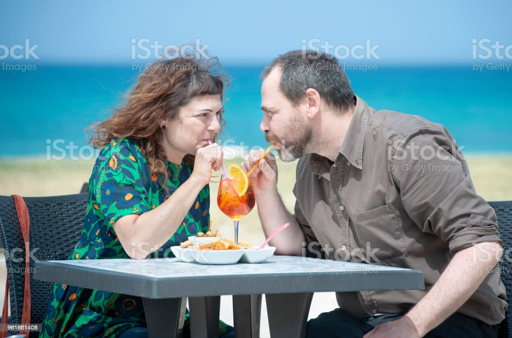 Couple of adults take an appetizer at the bar stock photo
