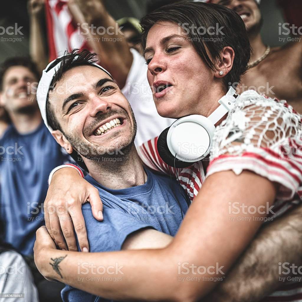 couple of american supporter at the stadium embracing royalty-free stock photo
