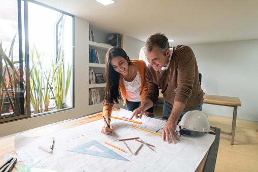 Portrait of a couple of architects working at the office drawing a blueprint and looking very happy