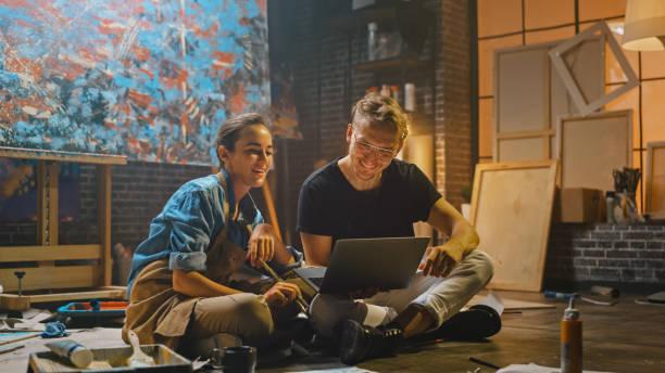 paar von künstlern sitzen in ihrem studio verwenden laptop-computer, arbeiten an einem projekt, sprechen und lächeln. malerund und ihr partner forschen. authentischer workshop mit ölgemälden und werkzeugen - maler gesucht stock-fotos und bilder